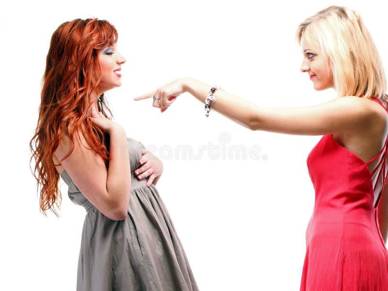 Uno zenzero delle due donne con il blonde in abiti su bianco fotografie stock