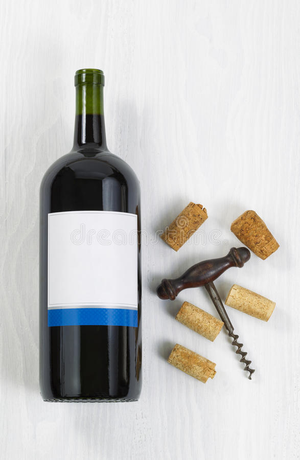 Unopened large bottle of red wine with an antique corkscrew and royalty free stock image