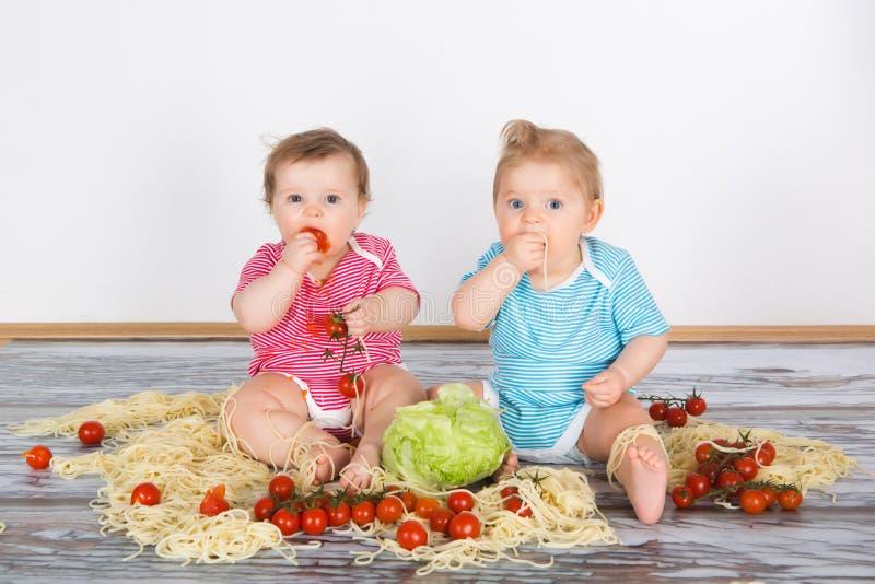 Unordentliche Babykleinkinder, die das Spaßessen haben stockbild