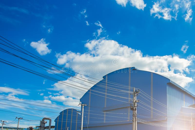Unordentliche elektrische Drahtseile mit Dach des Fabriklagergebäudes im Industriegebiet stockbild