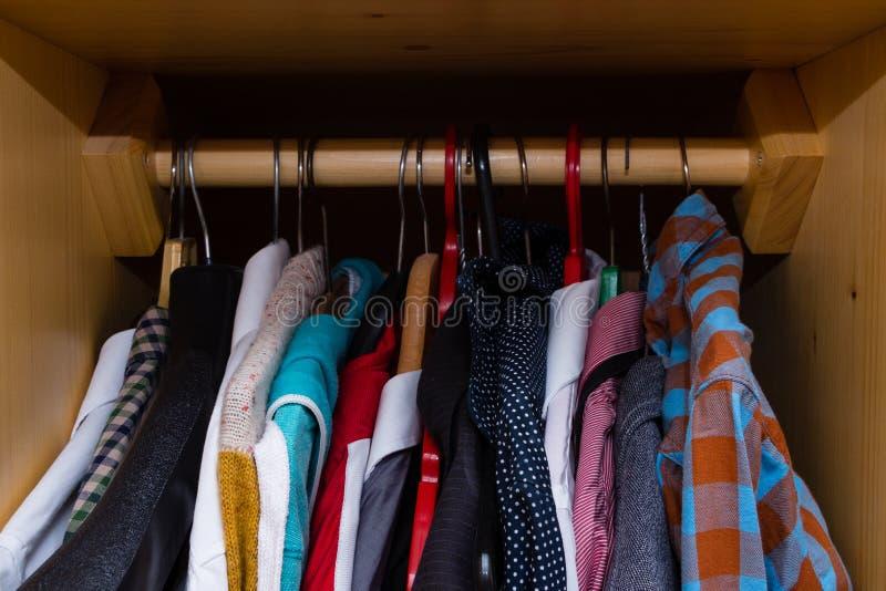 Unordentliche hölzerne Garderobe voll von Kleidung stockfotografie