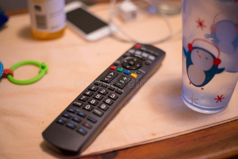 Unordentliche Tischplatte mit Fernbedienung, Wasserglas, Telefon, Dose, Ladegerät und dem Spielzeug der Kinder stockfotos