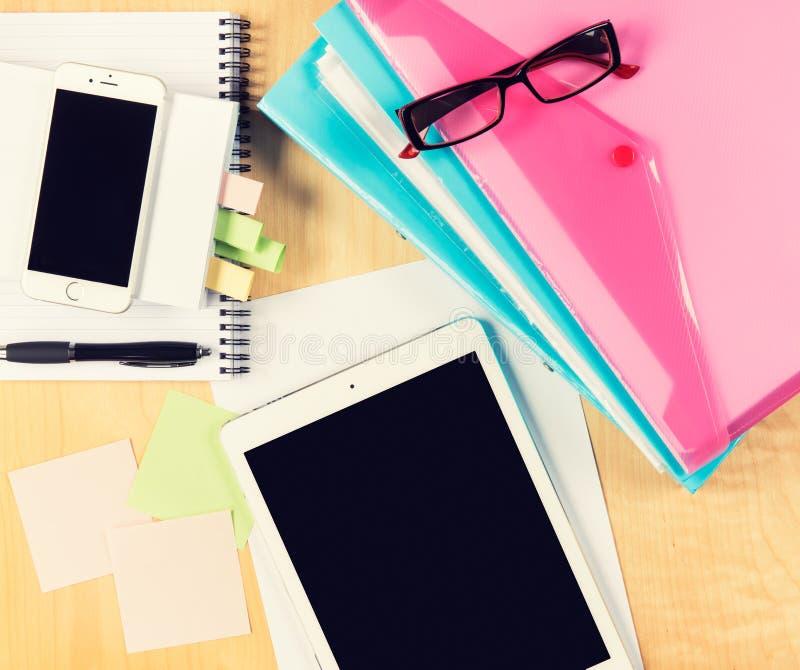 Unordentlicher Bürotisch mit digitaler Tablette, Smartphone, Lesebrille, Notizblock und füllenden Ordnern Ansicht von oben lizenzfreies stockfoto