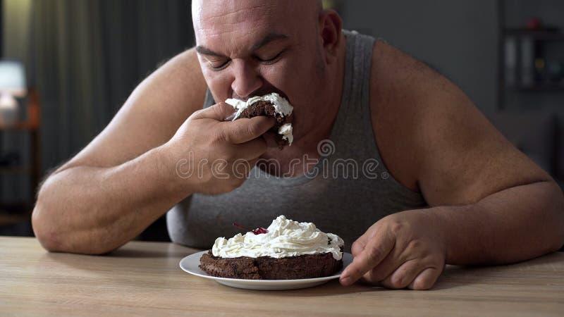 Unordentlicher beleibter Mann, der gierig Kuchen mit Schlagsahne, Sucht zu den Bonbons isst lizenzfreie stockfotografie