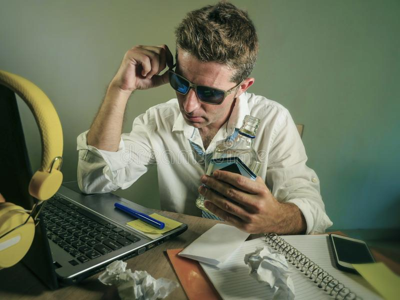 Unordentlicher Geschäftsmann, der schauenden Alkohol-Wodkaflasche Laptop-Computer Schreibtischs an der trinkenden niedergedrückte lizenzfreie stockfotos