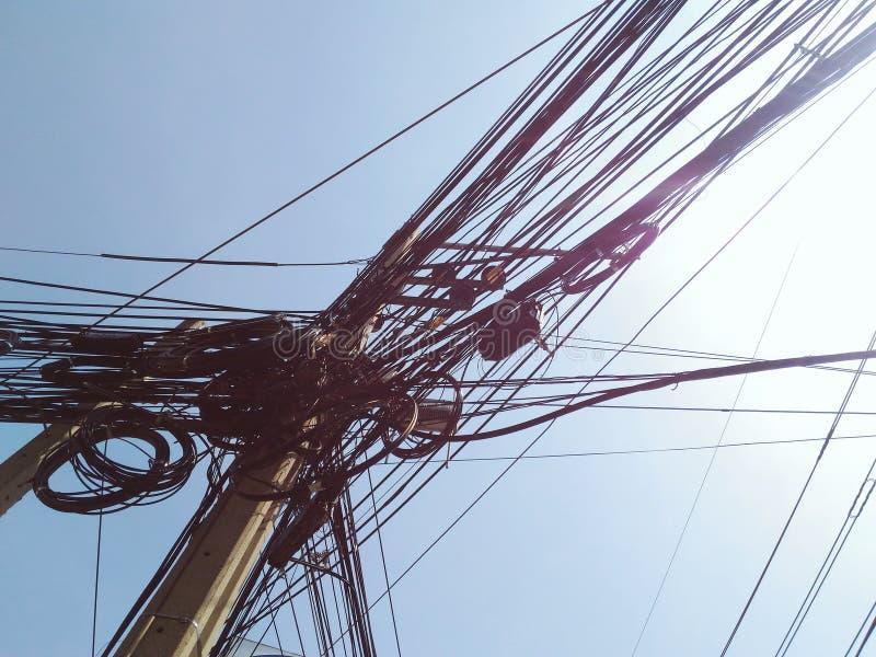 Unordentlicher Kabeldraht auf elektrischem Pfosten gegen blauen Himmel stockfotografie