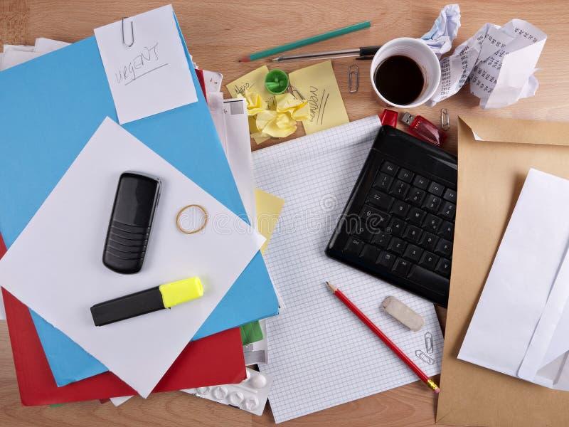 Unordentlicher, unordentlicher Schreibtisch - Überlastung lizenzfreie stockbilder