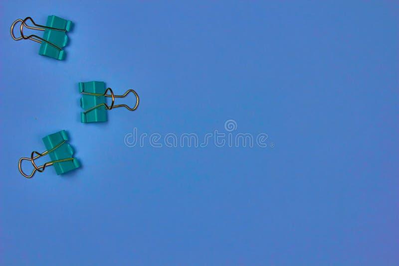 Unos pocos clips azules en un fondo colorido con espacio para copiar texto fotografía de archivo