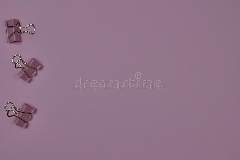 Unos pocos clips de papel rosa en un fondo rosa con espacio para copiar texto imagen de archivo libre de regalías