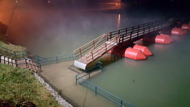 Unosi się pontonowy most przy mgłową nocą podczas powodzi i zdjęcia stock