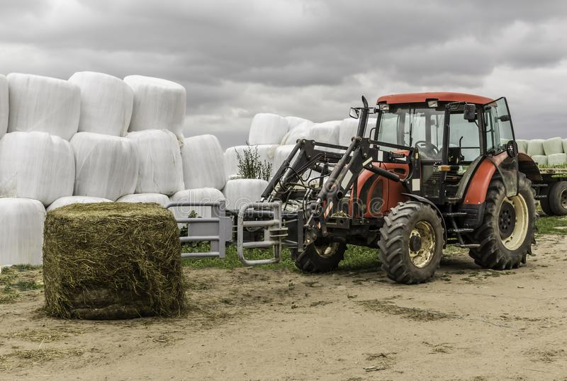Unpacked from the membrane a silage bale and a tractor with a forklift. royalty free stock photo