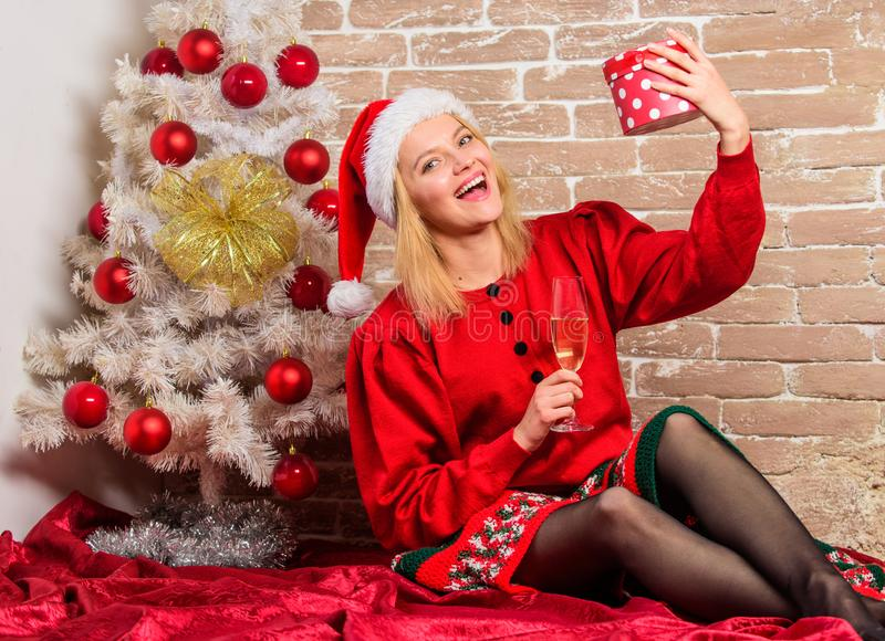 Unpacking christmas gifts. Winter holidays concept. Girl wear red dress sit near christmas tree. Woman hold glass. Champagne and gift box. Lady celebrate royalty free stock images