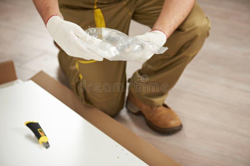 Unpacking plastic bag. Close-up in carpenter hands stock image