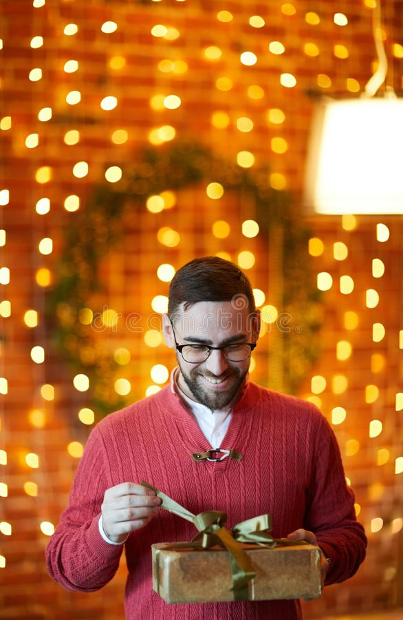 Unpacking surprise. Happy businessman untying golden ribbon on top of gift-box during Christmas party in office stock photos
