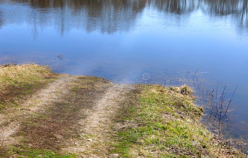 Unpaved rural road flooded by the river. Spring flooding of the river. Trees reflected in the water. For your design royalty free stock photography