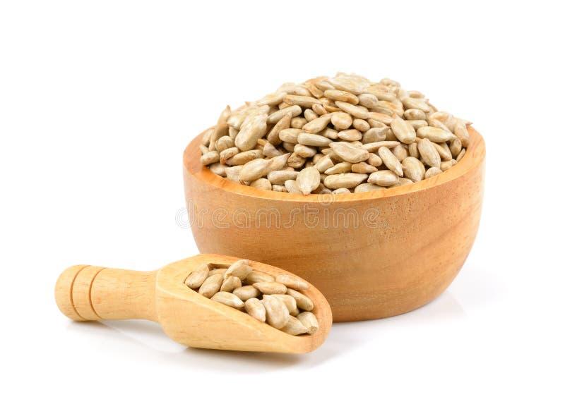 Unpeeled семена подсолнуха в деревянном шаре изолированном на белизне стоковое фото rf