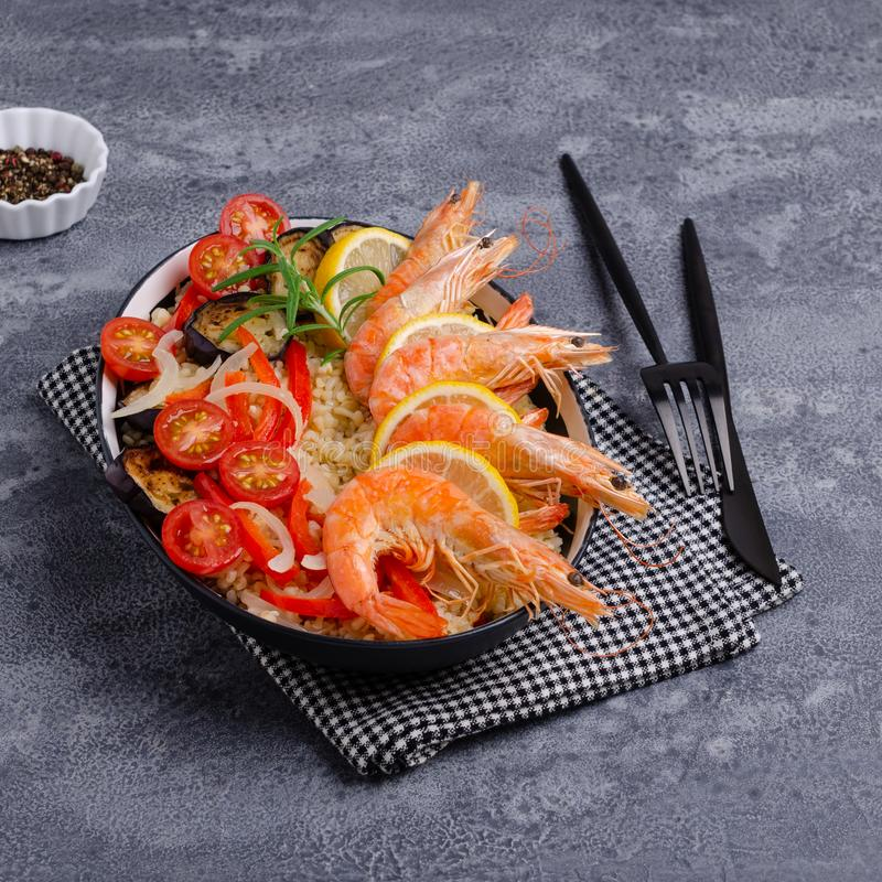 Unpeeled boiled shrimp with bulgur. And vegetables in a dish on a slate background. Selective focus royalty free stock photos