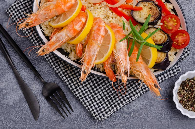 Unpeeled boiled shrimp with bulgur. And vegetables in a dish on a slate background. Selective focus royalty free stock photography
