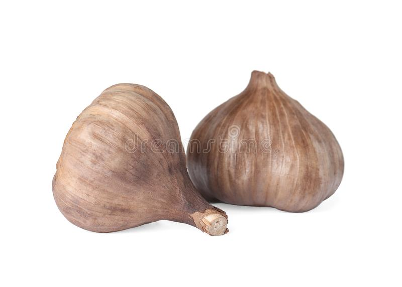 Unpeeled bulbs of black garlic on white royalty free stock photo