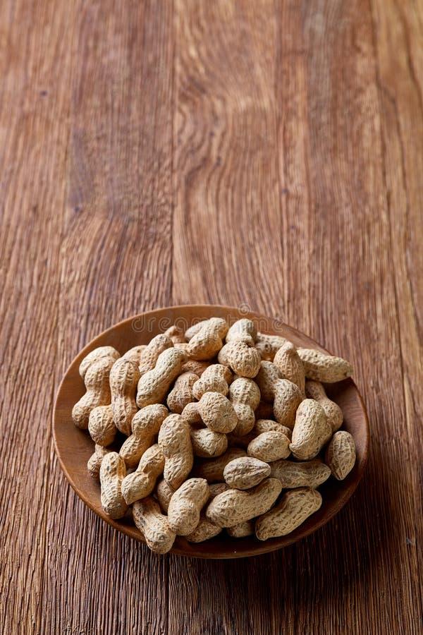 Unpeeled jordnötter i träbunke över den lantliga träbakgrundscloseupen, selektiv fokus arkivfoto