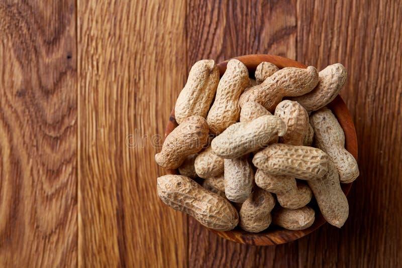 Unpeeled jordnötter i träbunke över den lantliga träbakgrundscloseupen, selektiv fokus royaltyfri foto
