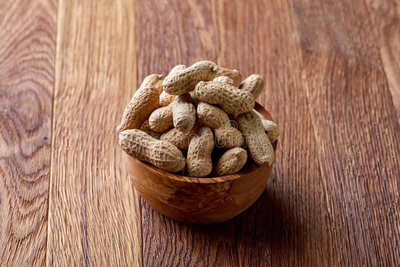 Unpeeled jordnötter i träbunke över den lantliga träbakgrundscloseupen, selektiv fokus royaltyfri bild
