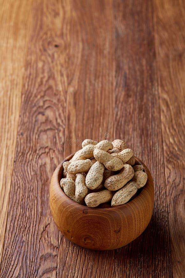 Unpeeled jordnötter i träbunke över den lantliga träbakgrundscloseupen, selektiv fokus royaltyfria foton