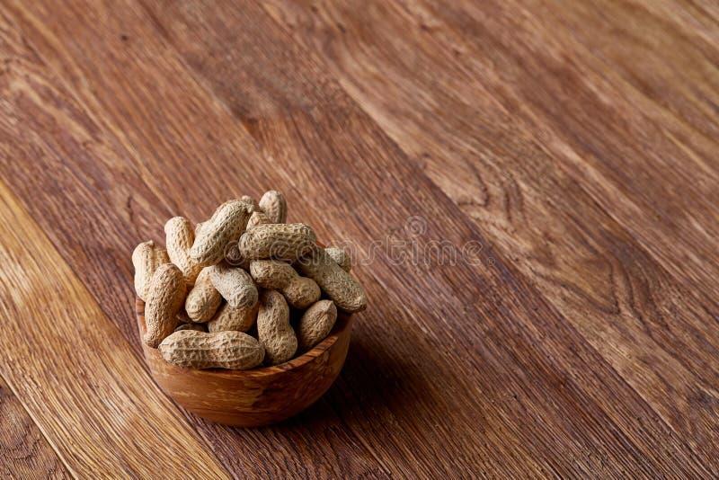 Unpeeled jordnötter i träbunke över den lantliga träbakgrundscloseupen, selektiv fokus royaltyfri fotografi