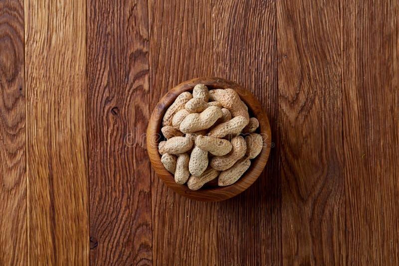 Unpeeled jordnötter i träbunke över den lantliga träbakgrundscloseupen, selektiv fokus arkivbilder