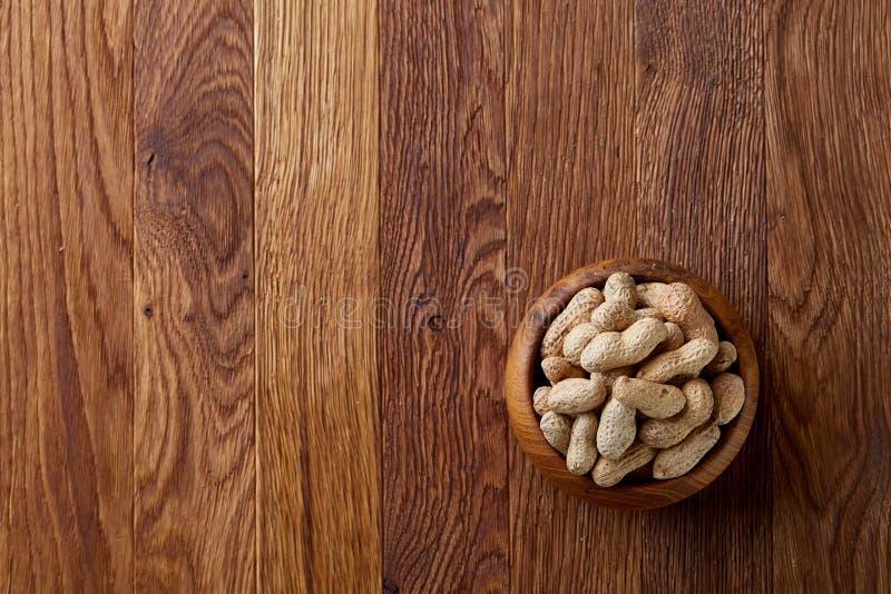 Unpeeled jordnötter i träbunke över den lantliga träbakgrundscloseupen, selektiv fokus arkivfoton
