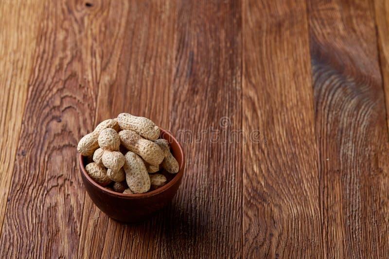 Unpeeled jordnötter i träbunke över den lantliga träbakgrundscloseupen, selektiv fokus royaltyfria bilder