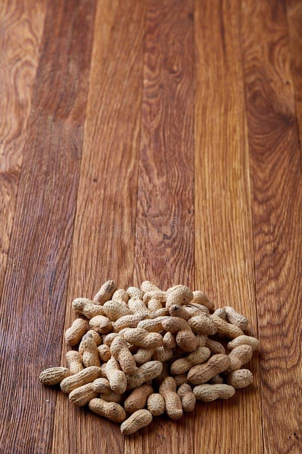 Unpeeled jordnötter på en träbakgrund, bästa sikt, selektiv fokus, grunt djup av fältet royaltyfri fotografi