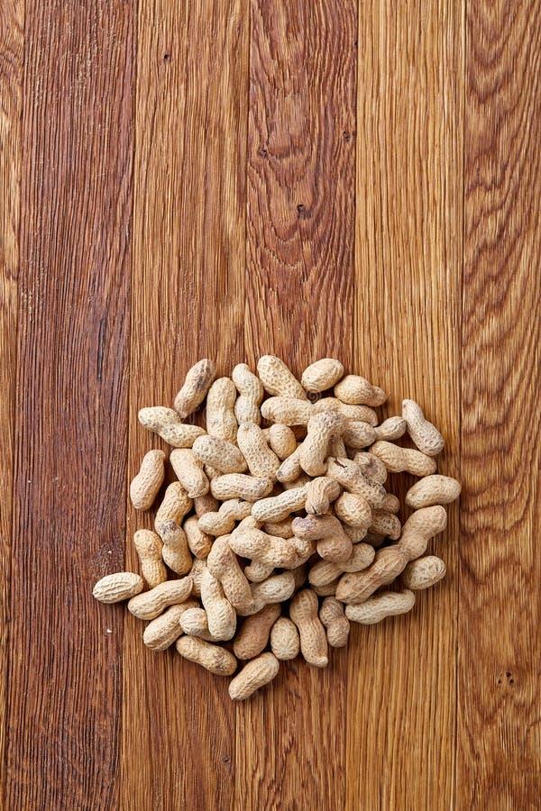 Unpeeled jordnötter på en träbakgrund, bästa sikt, selektiv fokus, grunt djup av fältet royaltyfri bild