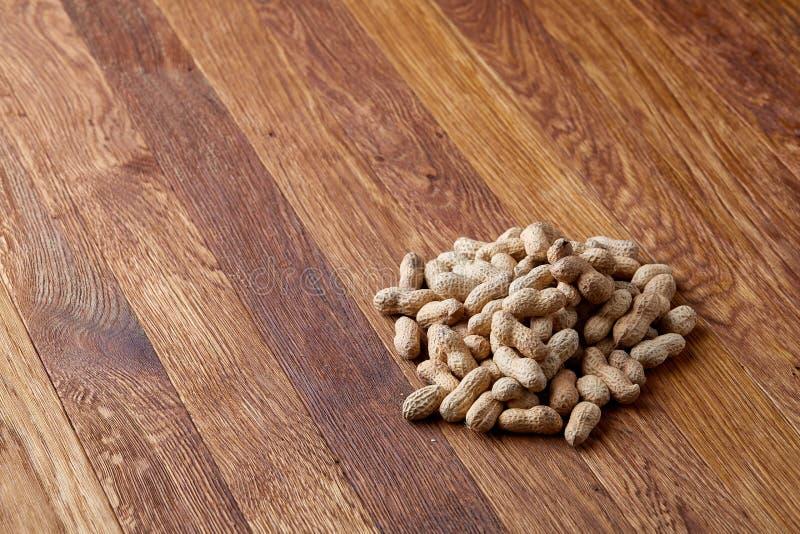 Unpeeled jordnötter på en träbakgrund, bästa sikt, selektiv fokus, grunt djup av fältet arkivfoton