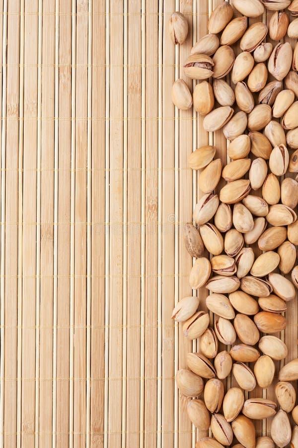 Unpeeled pistascher som ligger på en matt bambu royaltyfri fotografi