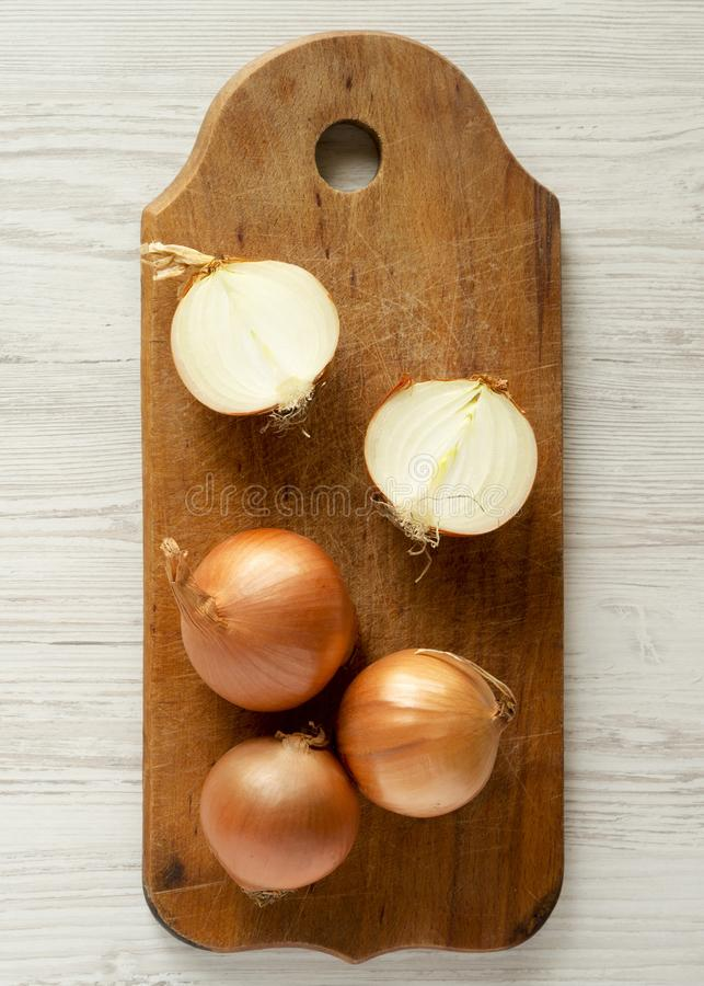 Unpeeled raw organic yellow onions on rustic wooden board over white wooden background, top view. Flat lay, overhead, from above. royalty free stock images