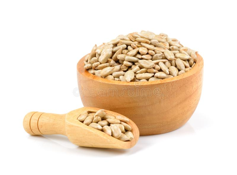 Unpeeled sunflower seeds in wooden bowl isolated on white royalty free stock photo