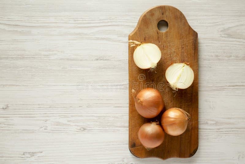 Unpeeled surowe organicznie żółte cebule na nieociosanej drewnianej desce nad białą drewnianą powierzchnią, odgórny widok Mieszka zdjęcia royalty free