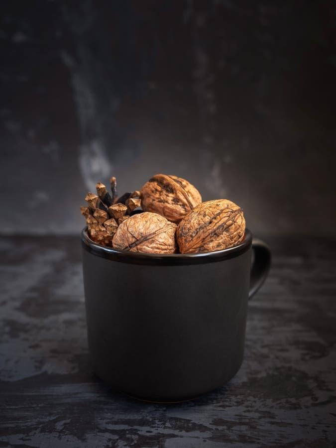 Unpeeled walnuts in a black ceramic mug closeup royalty free stock photo