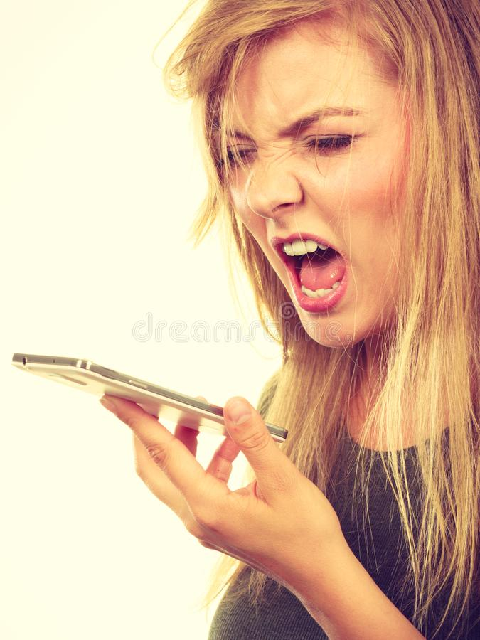Angry young woman talking on phone. Unpleasant conversation, bad relationships concept. Screaming furiously angry young blonde woman talking on phone royalty free stock photos