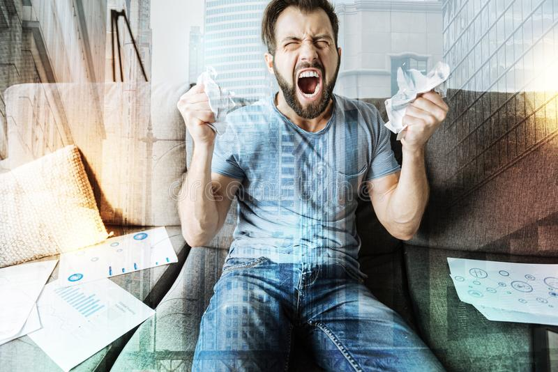 Unpleasant crapping man sitting and screaming. Just not that. Unpleasant beardful crapping man sitting in the room on the sofa tearing the paper and screaming royalty free stock photography