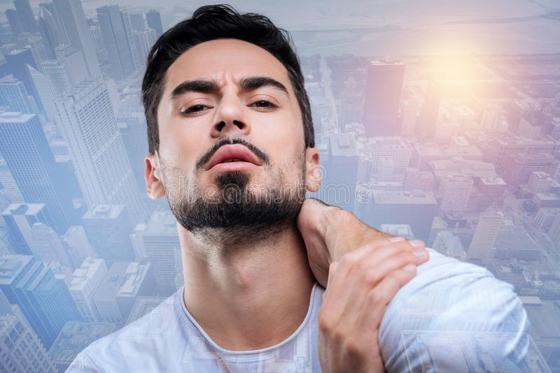 Serious bearded man touching his neck and frowning. Unpleasant feeling. Attentive serious worried man noticing a strange pain in his neck while touching it and stock image