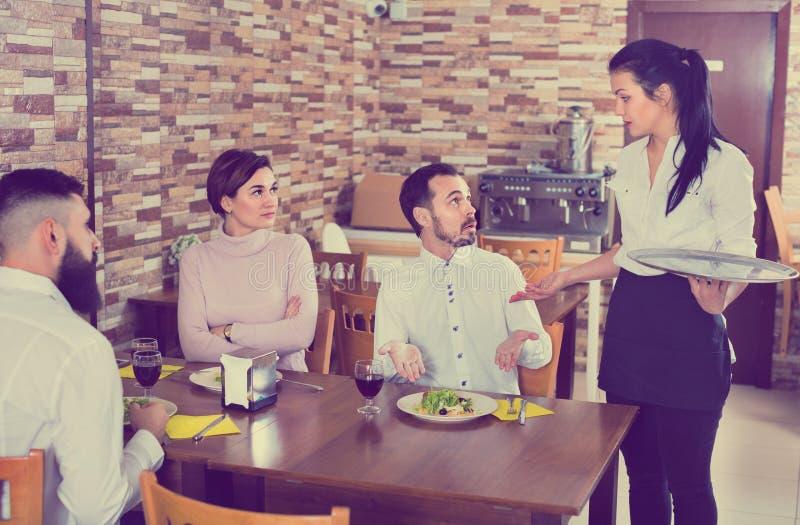 Unpleased客户谈话与经理在餐馆 免版税库存图片