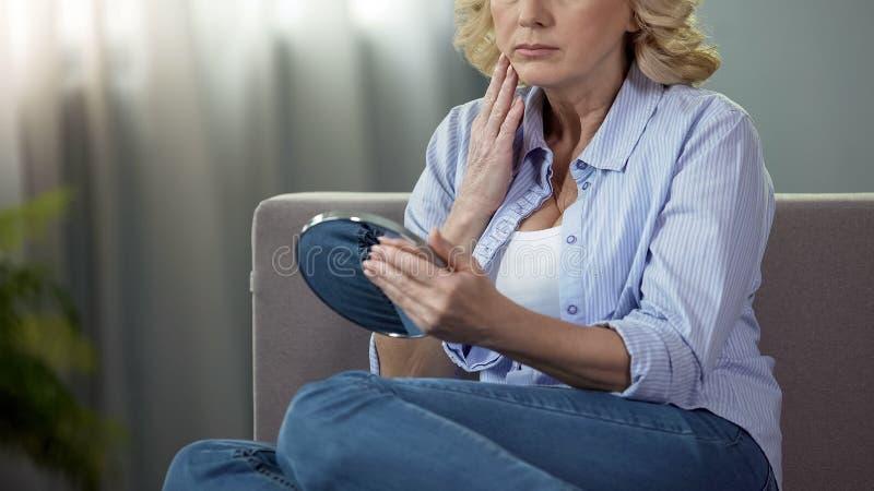 Unpleased выбыло женщину сидя на кресле и смотря в зеркало руки, время стоковое изображение rf