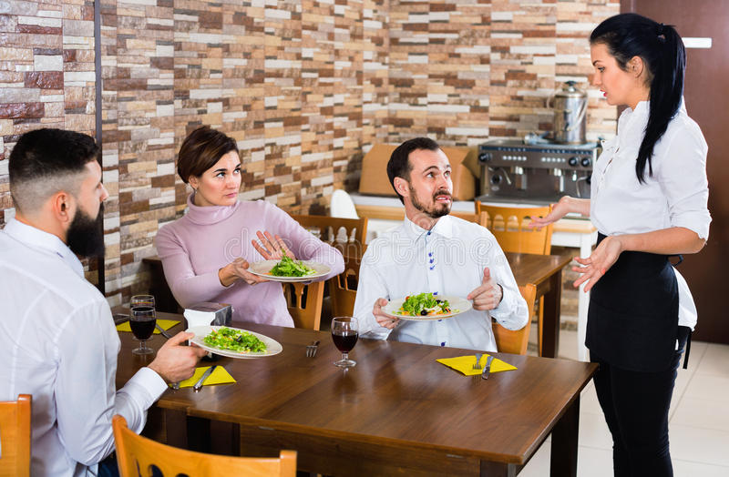 Unpleased client talking with manager in restaurant. Young unpleased angry ordinary couple doesn`t like the service and food at cafe royalty free stock image