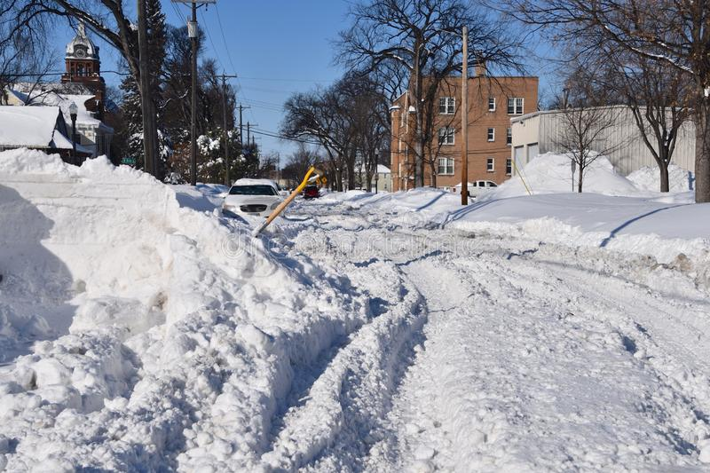 Snow ruts on a street after a snowstorm. An unplowed street in a city with ruts finds ruts and tracks made by vehicles driving after a heavy snowfall stock images