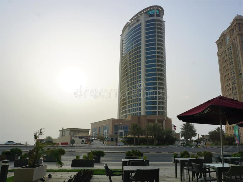 Unpopulated outdoor seating at Costa Coffee overlooking Hilton hotel. Empty chairs and tables line the street of Doha, Qatar in the early morning heat and royalty free stock photography
