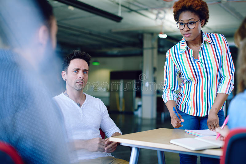 Unposed group of creative business people in an open concept office brainstorming their next project. stock images