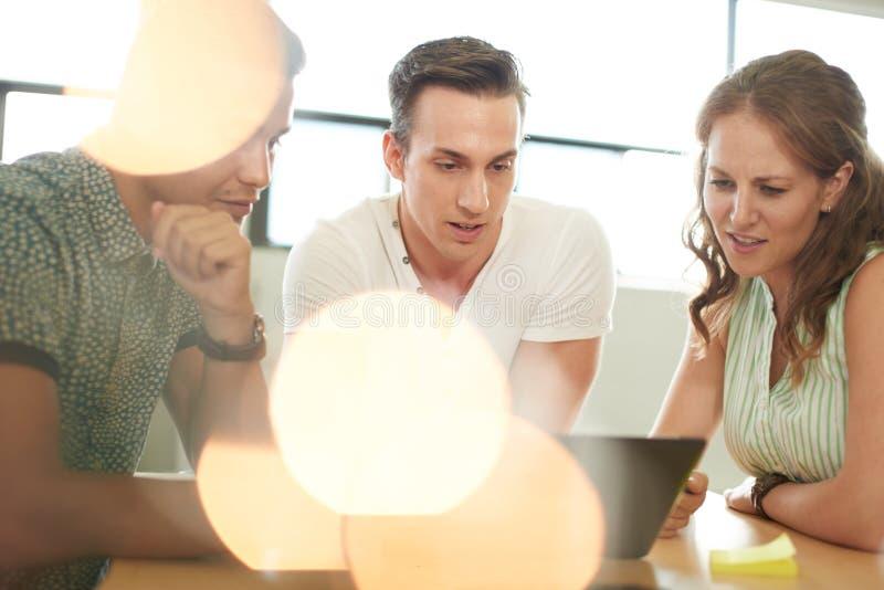 Unposed grupp av idérika affärsentreprenörer i en öppen begreppskontorsidékläckning tillsammans på en digital minnestavla arkivbild