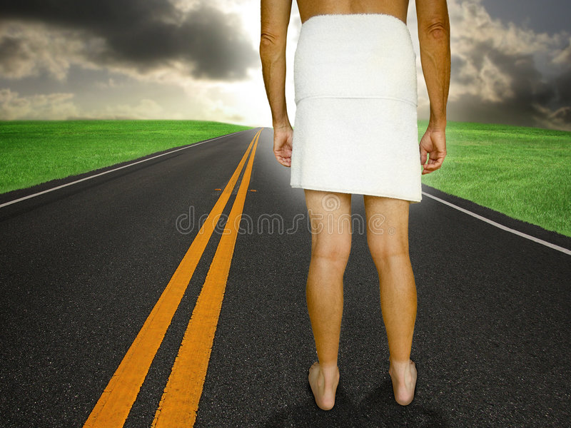 Unprepared. Man in towel is standing on a black top asphalt road with double yellow lines looking into the horizon. concept for being ready for the future or royalty free stock photography